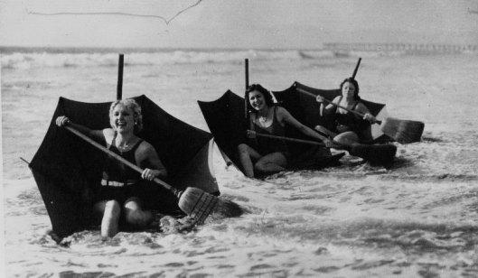 Acmé,  Sur une plage de Floride, jeunes filles se faisant porter par leur parapluie renversé formant un bateau et se servant d'un balai comme rame, 1932, photographie, Gallica/BnF